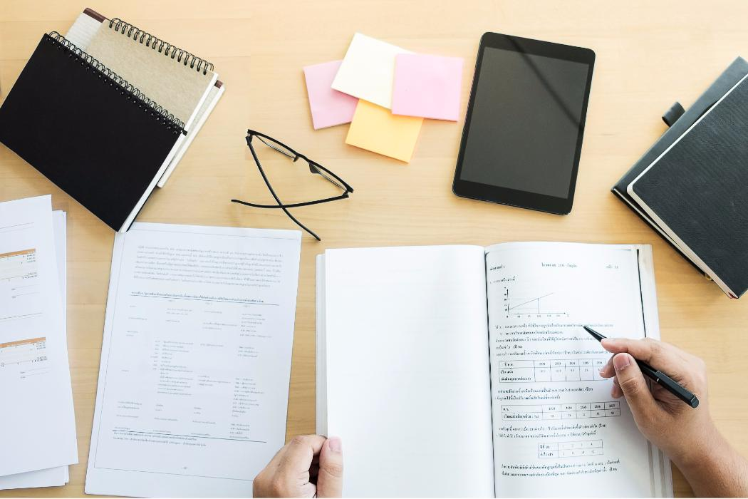 Desk with glasses, notebook and test paper being marked