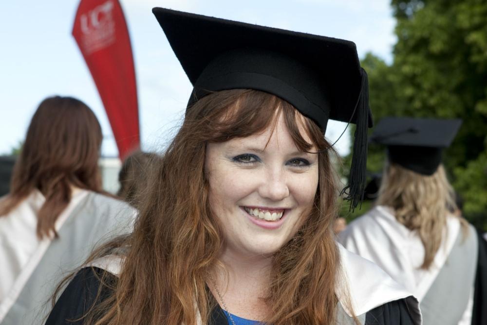 Student in regalia smiling at graduation ceremony