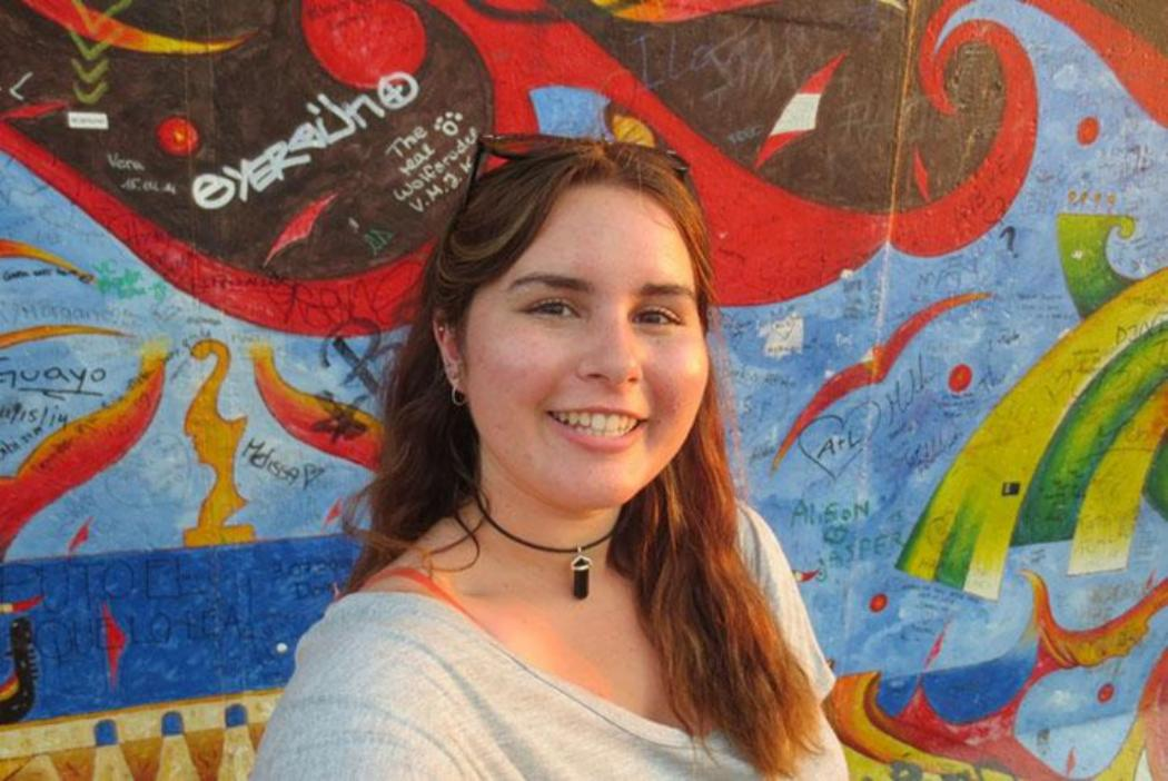 girl smiling standing in front of street art