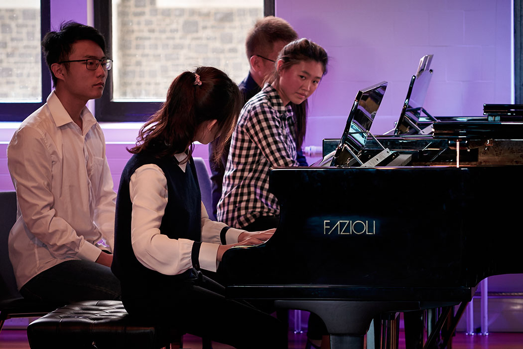 Two students playing piano