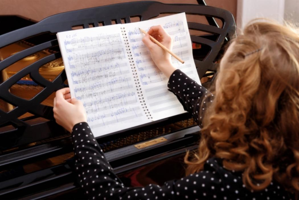 Music student seated at piano writing notes on sheet