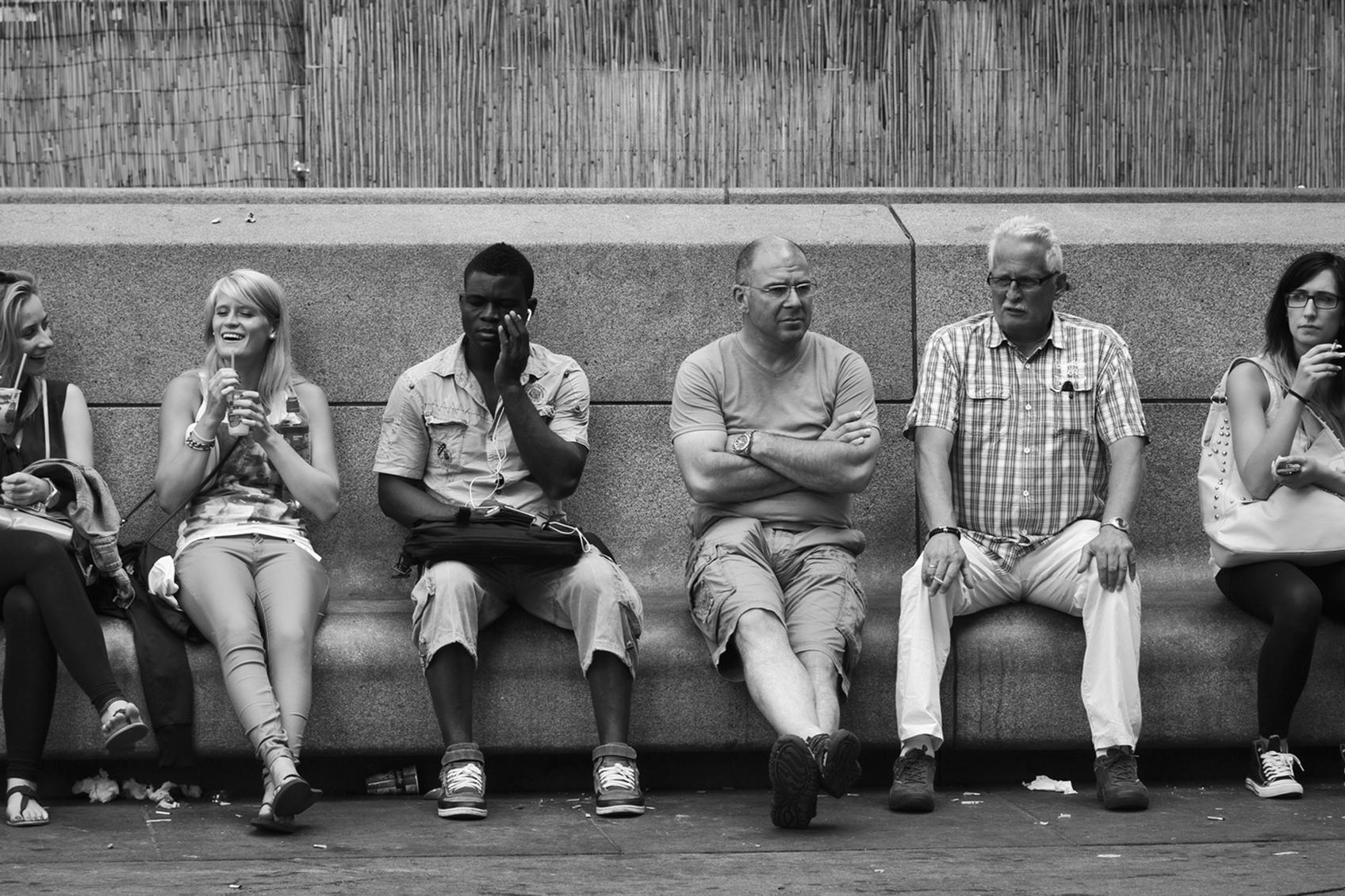 Black and white image of a culturally diverse group of people sitting side by side.