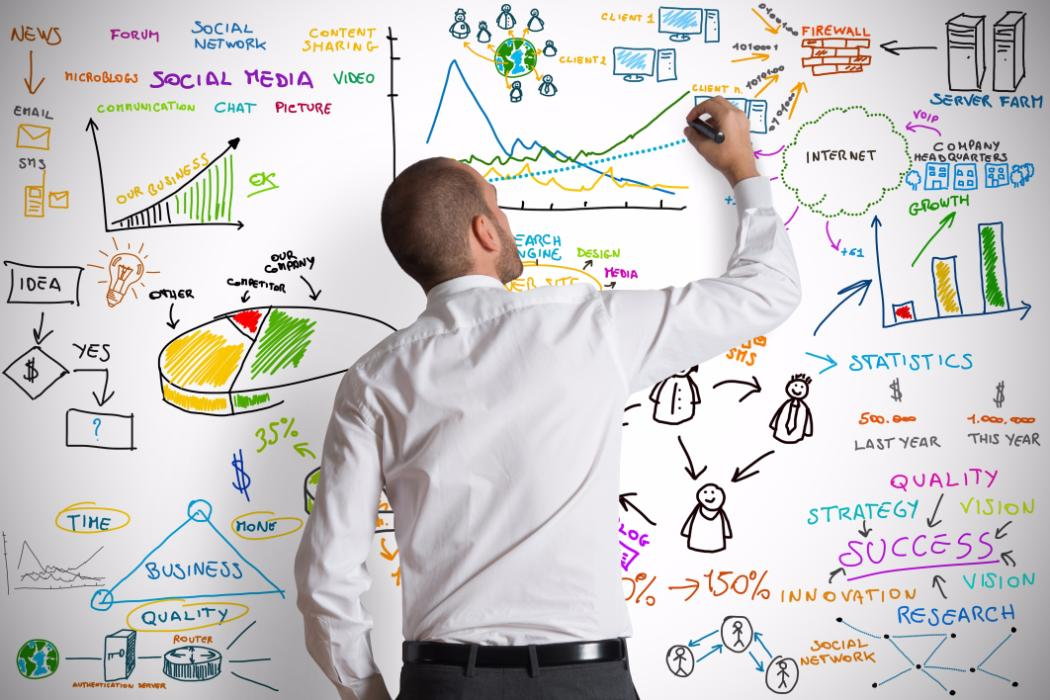 Man drawing on whiteboard different business related ideas, charts and graphs