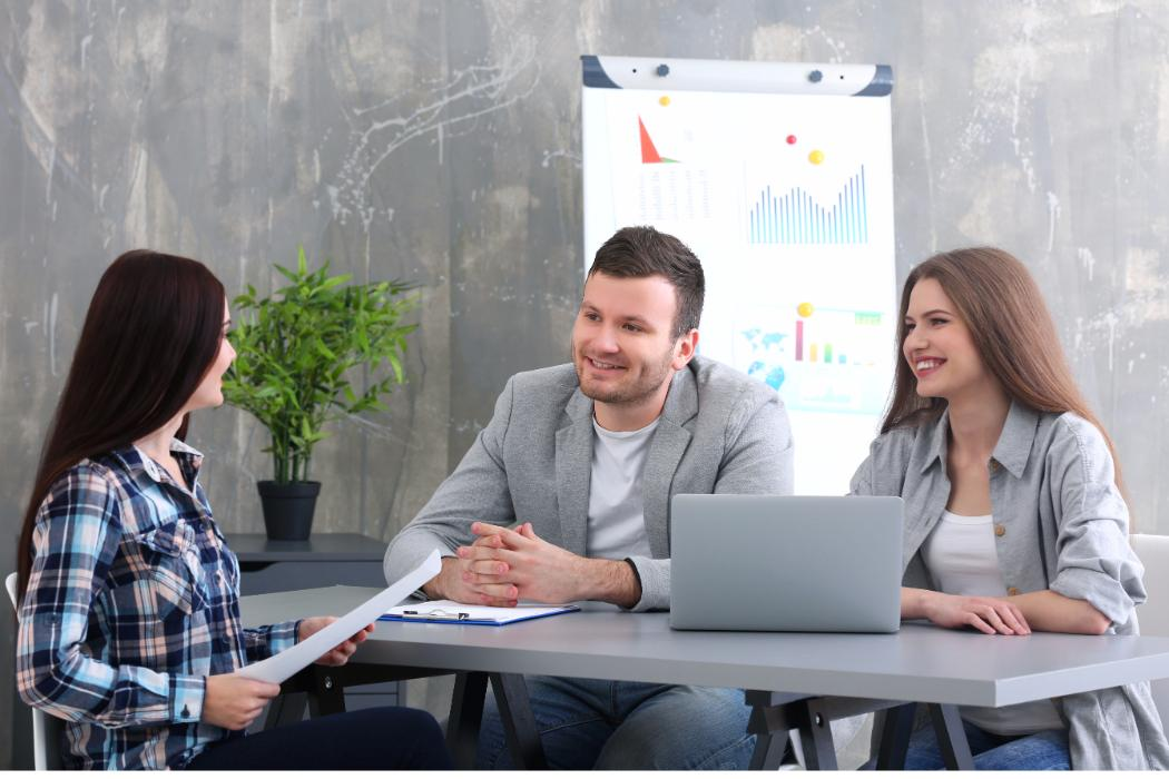 young entrepreneurs at table in boardroom with charts
