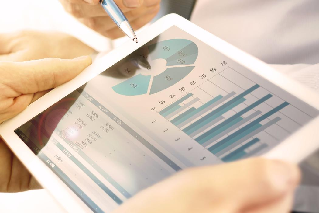 hands holding table with business graphs on screen