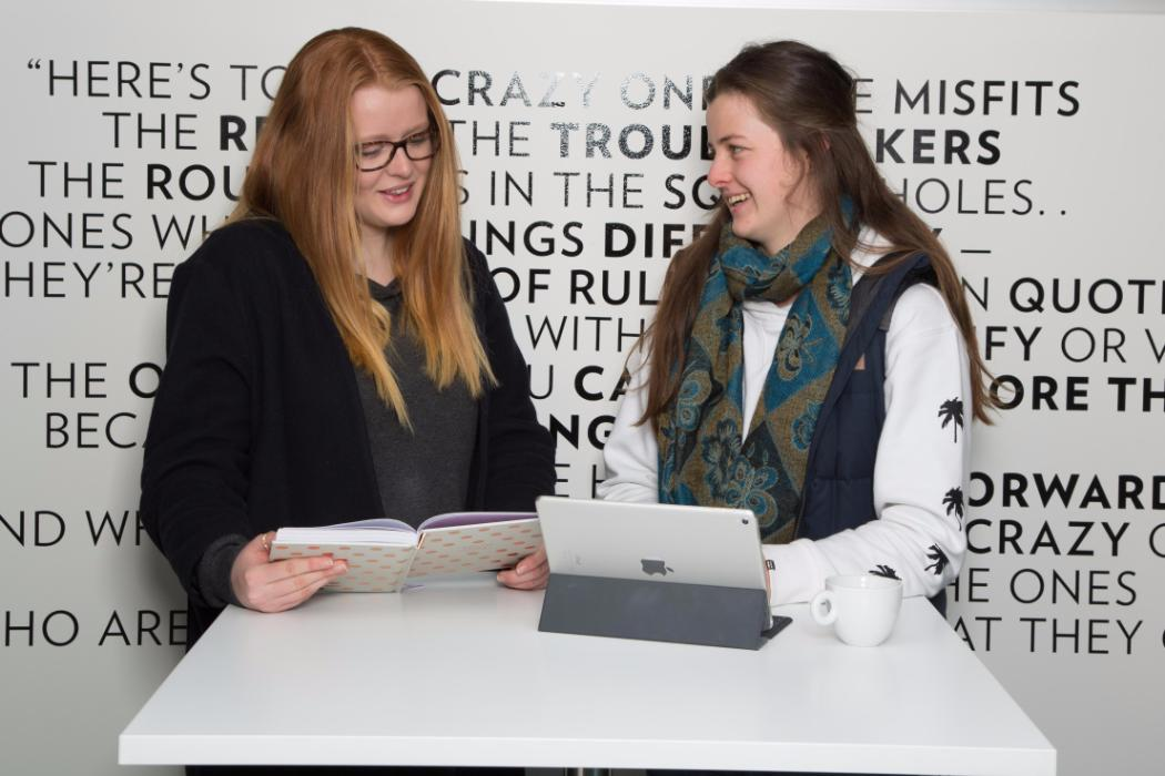 student entrepreneurs with laptop and book