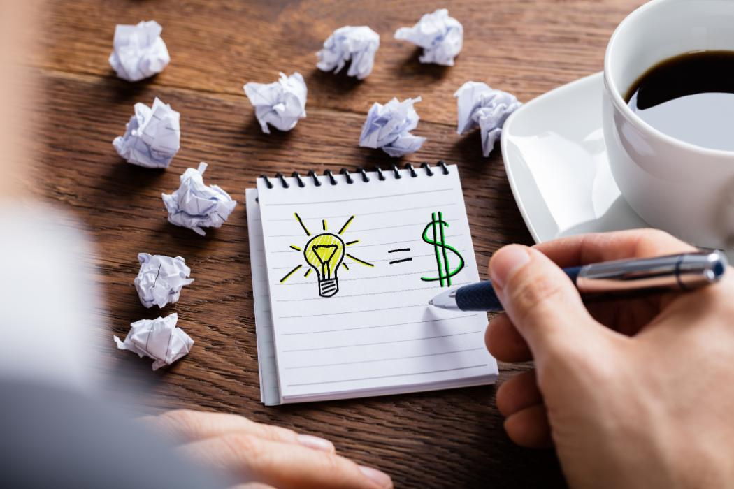 Man drawing a light bulb and dollar sign in a note book with coffee