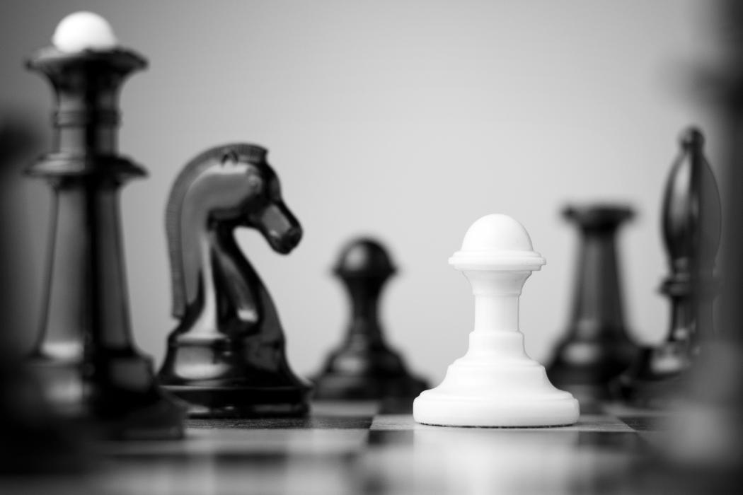 white pawn on chessboard surrounded by black pieces