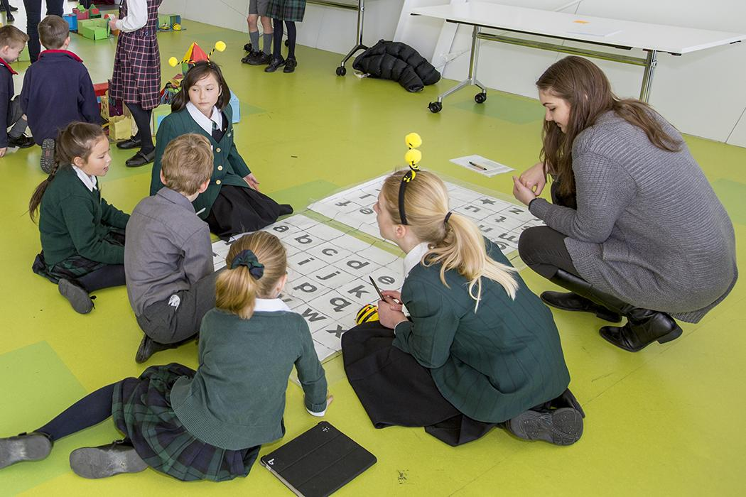 school children and instructor doing education activity on the floor