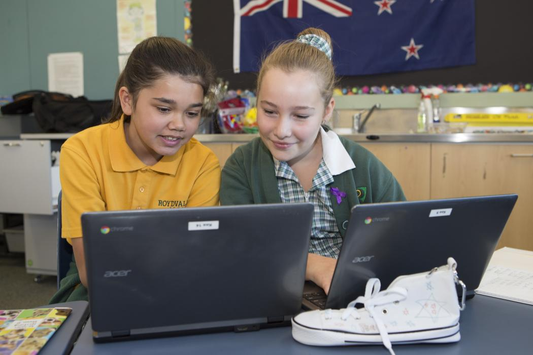 Two schoolgirls with laptops in a classroom