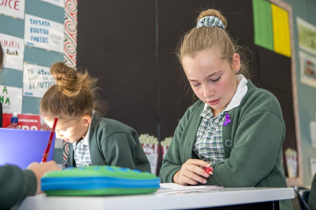 school girls doing work at a classroom desk