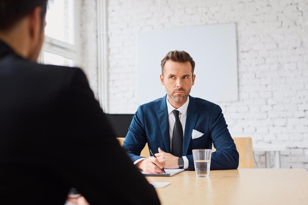 Man writing notes in interview