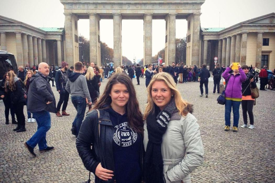 Girls smiling in front of the Brandenburg Gate in Berlin