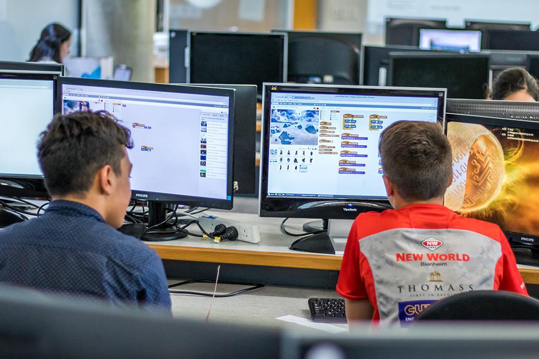 school boys doing educational activities facing a computer screen