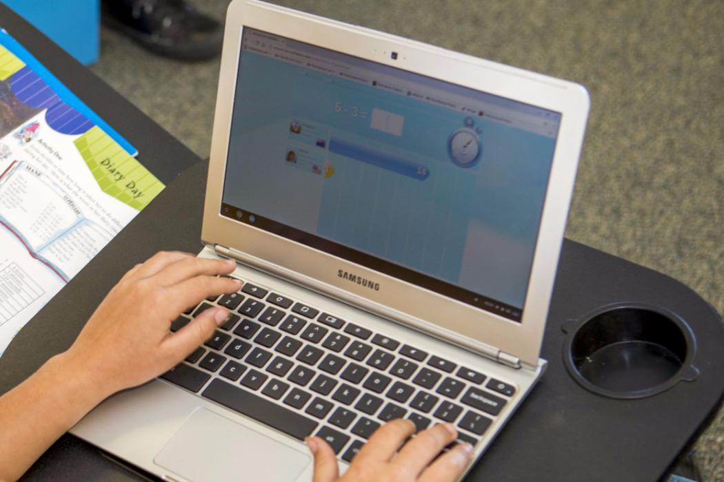 child's hands on laptop doing school work