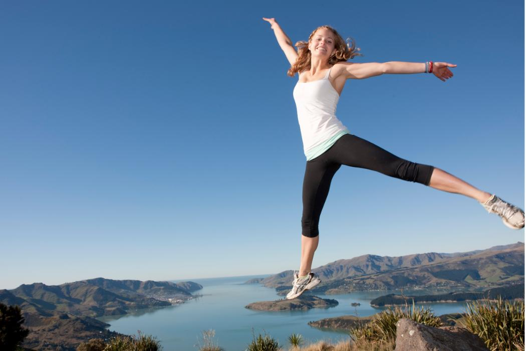 young woman jumping for joy at top of hills with harbour in background