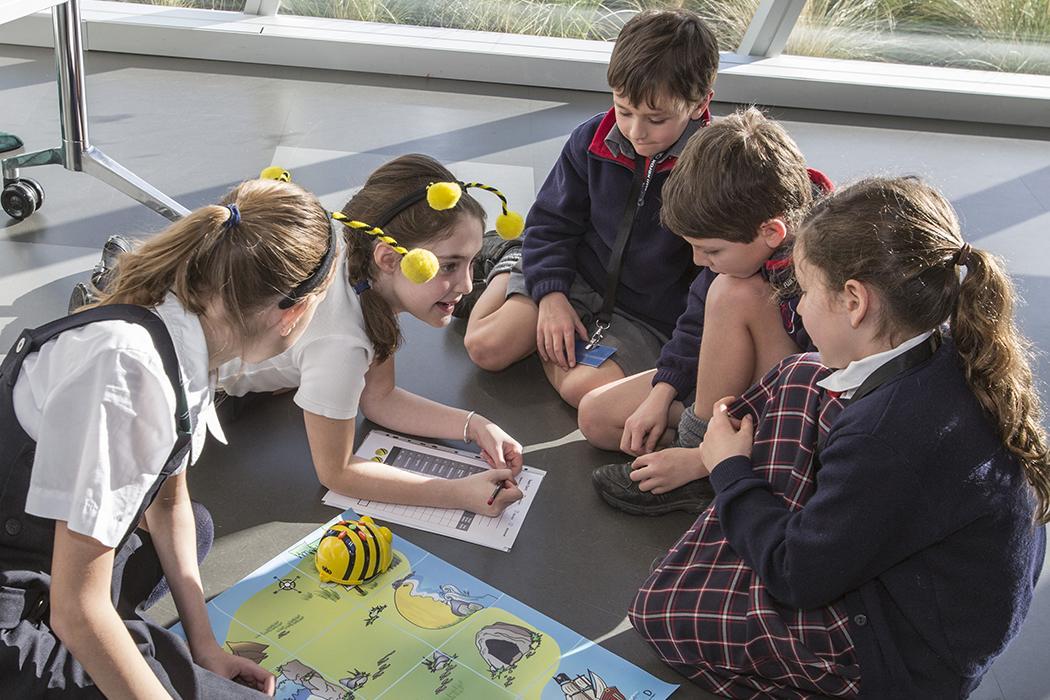 school children doing group activities on the floor