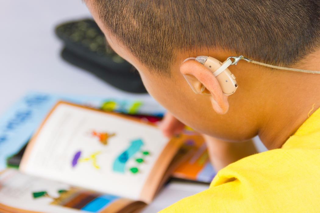boy with hearing aids and reading book
