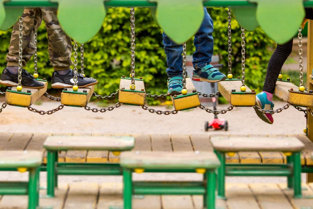 children's feet on a swinging bridge in playground