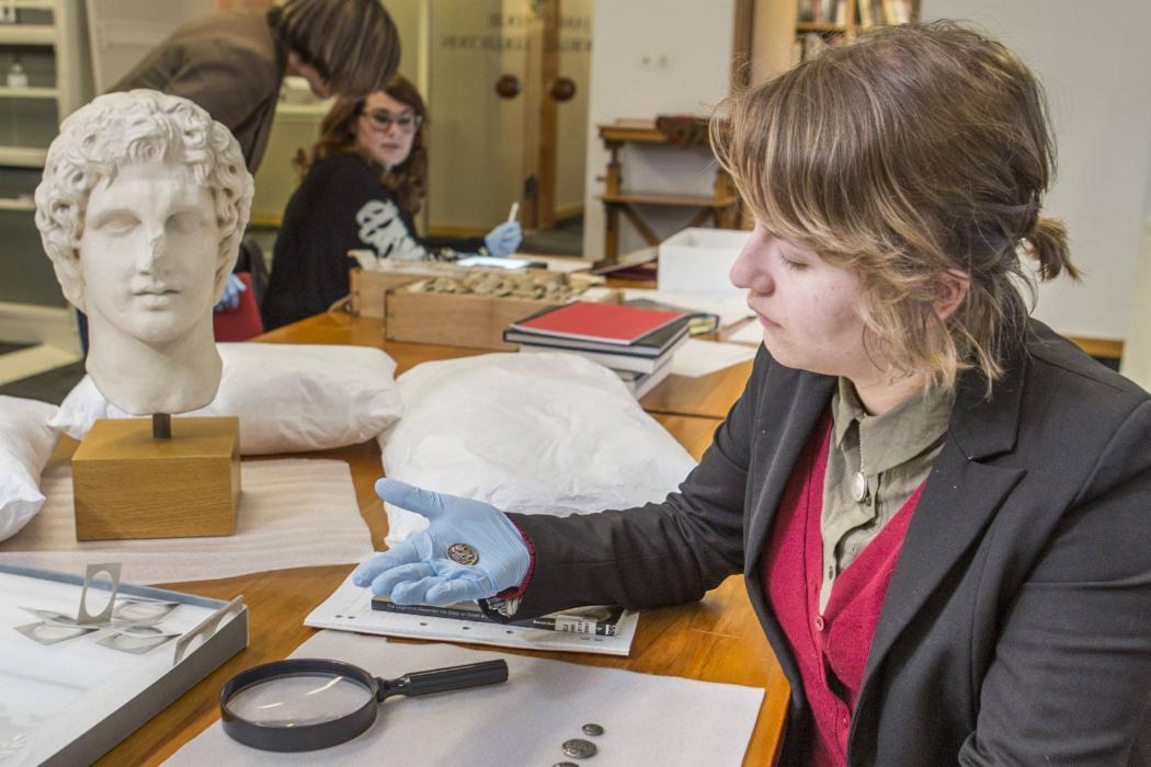 Female student examining coin near statue head