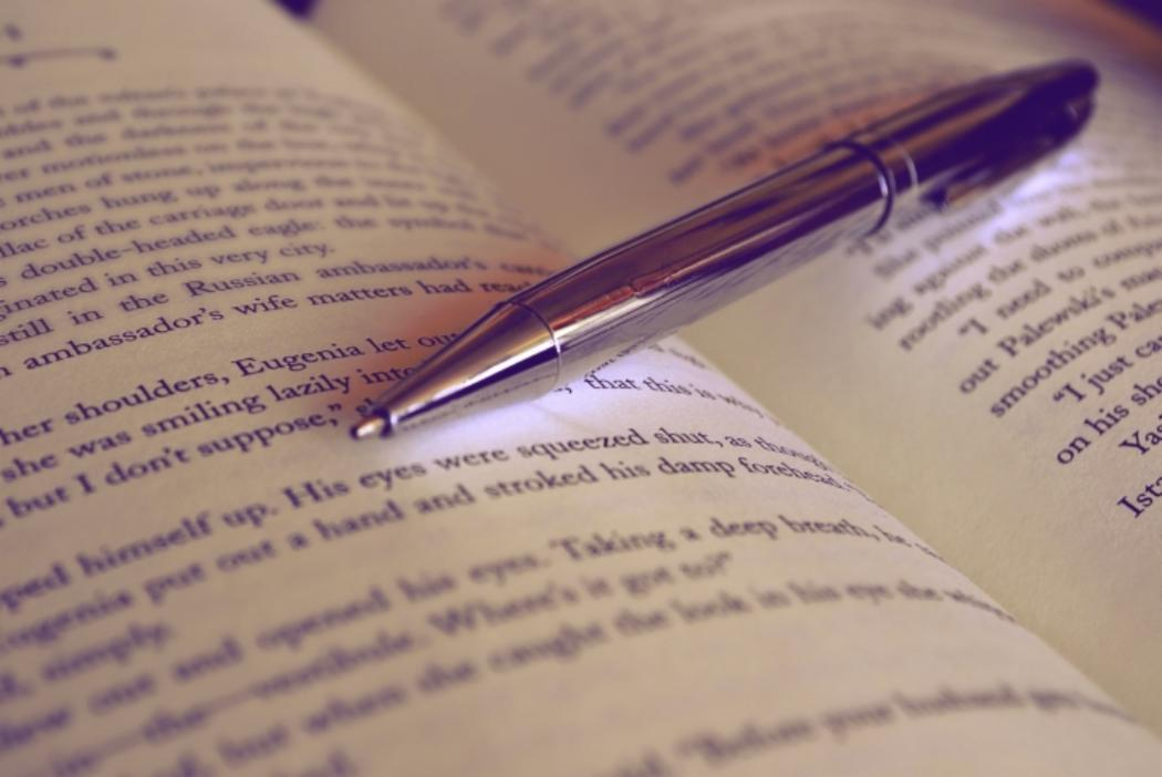 A quill pen placed on an opened book