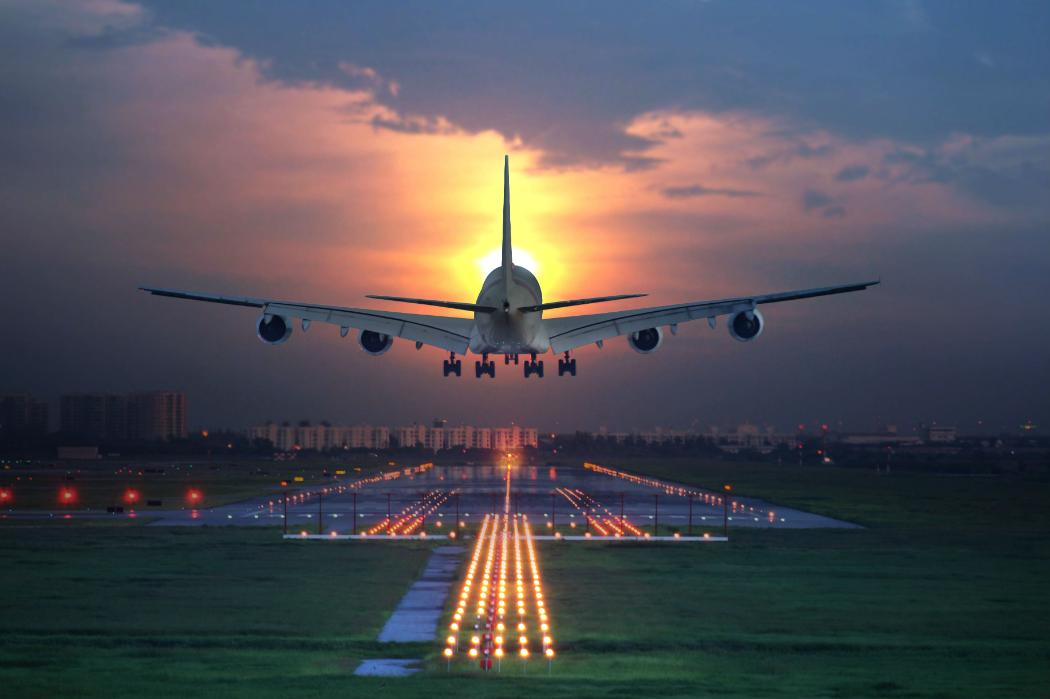 airplane landing on airport runway sunset