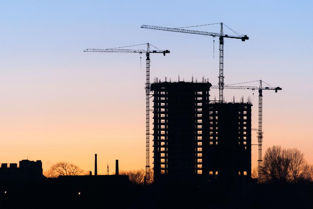 crane silhouetted at construction site at sunset