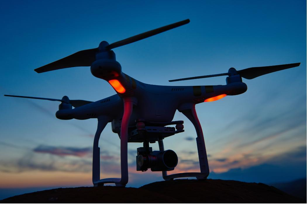 quad copter drone with camera at sunset