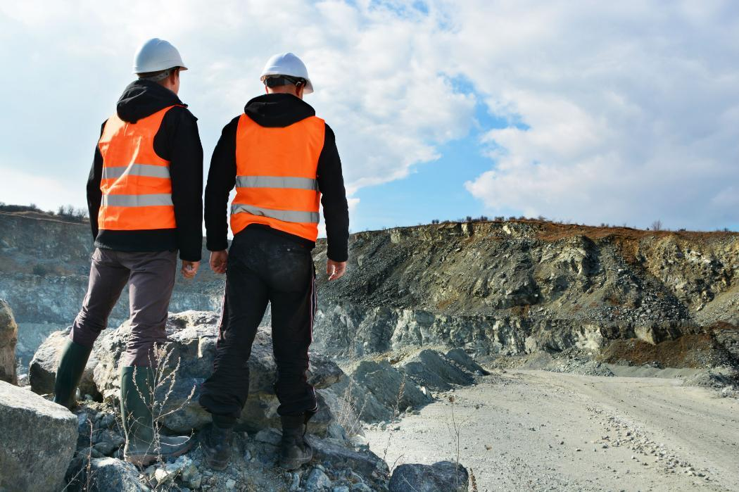Two men in high vis vests standing in open top mine