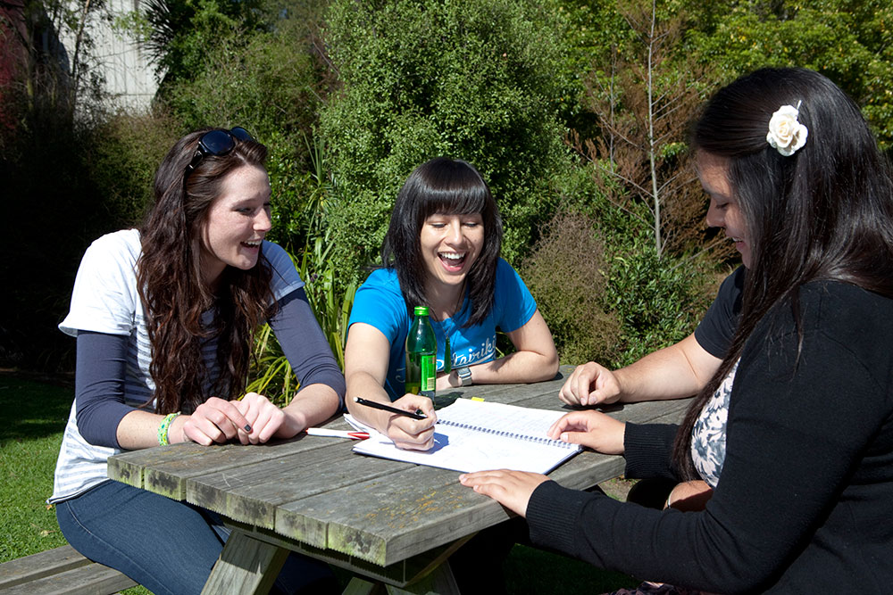 Maori students studying outside picnic table laughing landscape