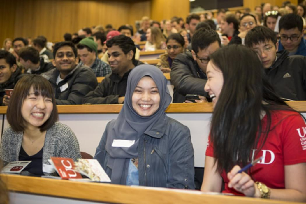 26 three students smiling front row lecture theatre