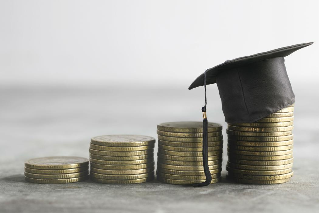 Stacked Coins with Academic Cap on top
