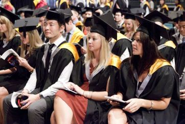 students sitting yellow graduation robes