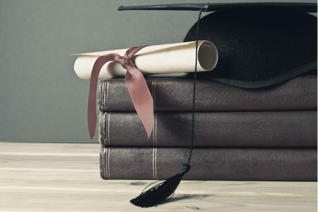 graduation cap resting on pile of books