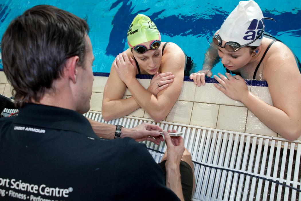 swimming coach with athletes in pool