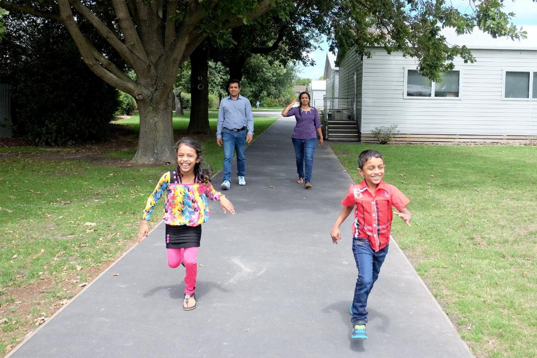 Happy kids running on pathway as parents follow