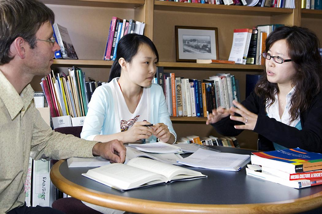 Agent explaining to potential students in library