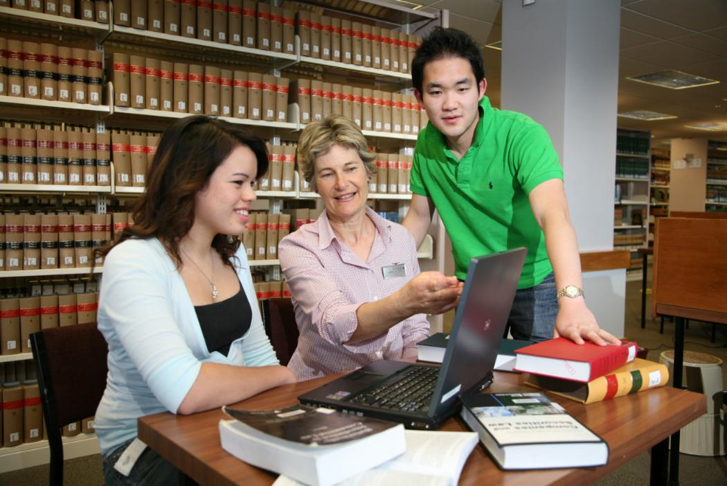 male and female student sitting with teacher in library in front laptop and book