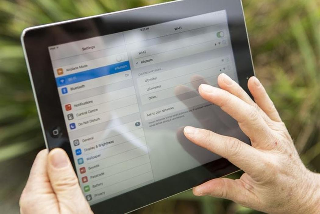 Hands holding iPad showing the wifi settings screen