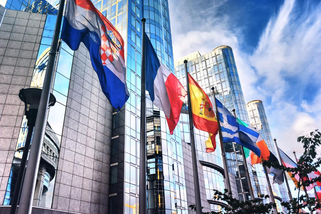 Multi-national flags infront of multi-story modern buildings