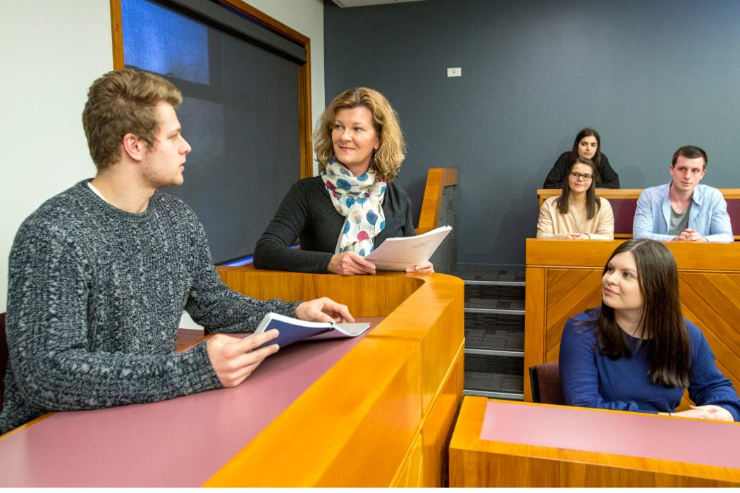law lecturer with senior students in moot court