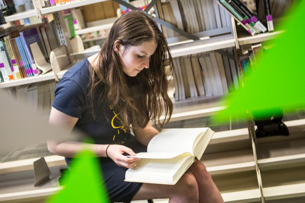 Female student looking at book in library