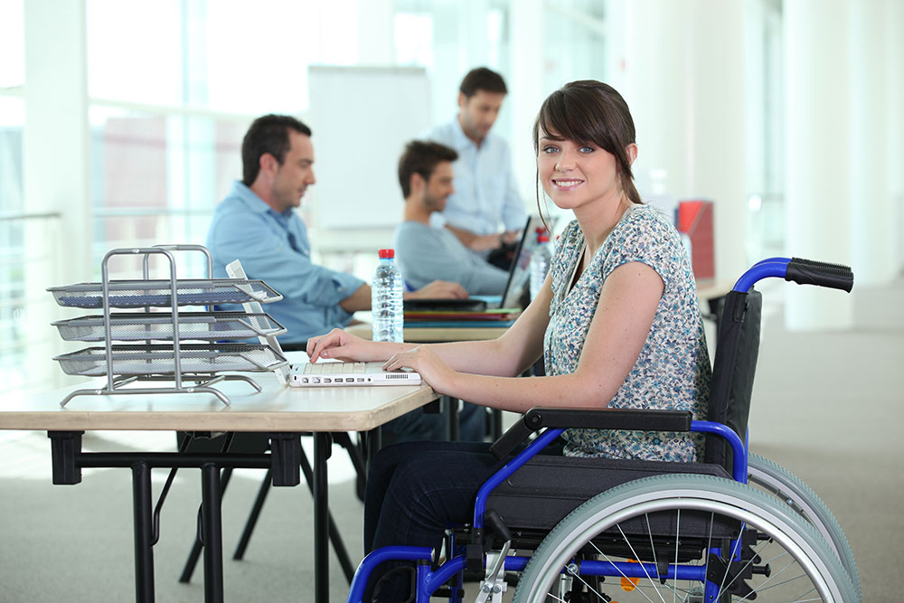 Woman in wheelchair with laptop computer Depositphotos 7779362
