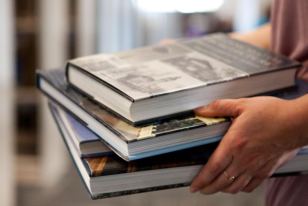 Hands holding stack of books landscape
