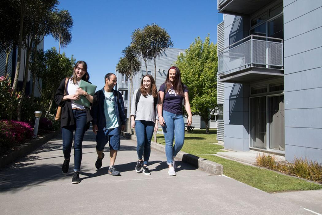 Ilam Apartments - students walking outside smiling
