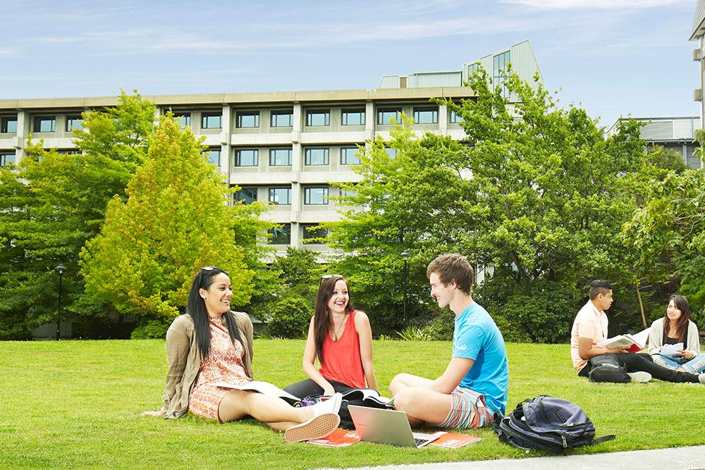 Campus 3 lawn sitting students landscape
