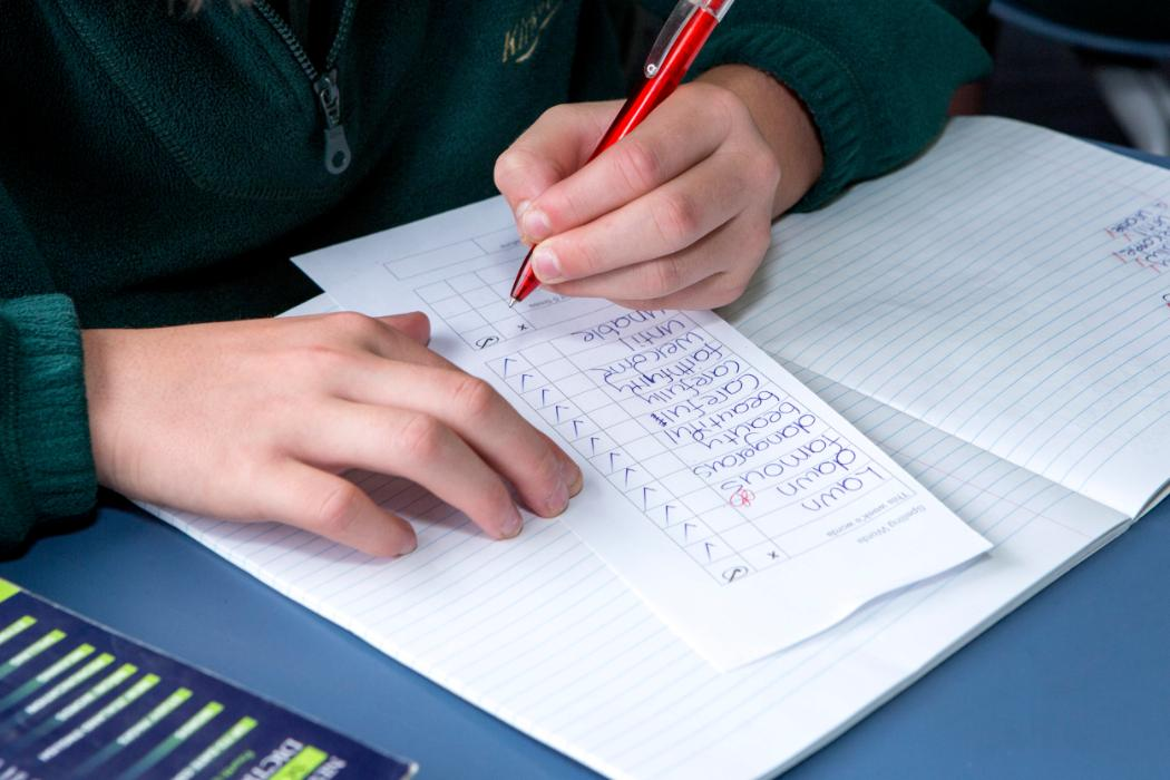 student's hands checking spelling list in class