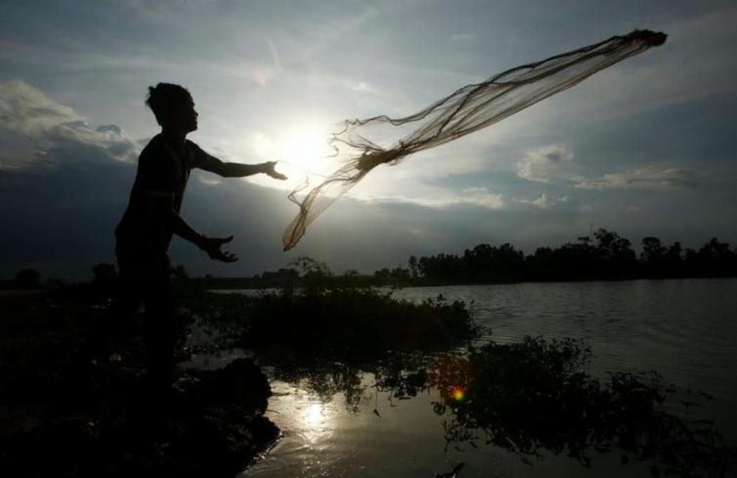 A man casts a fishing net onto a flooded land following rain to catch fish on th
