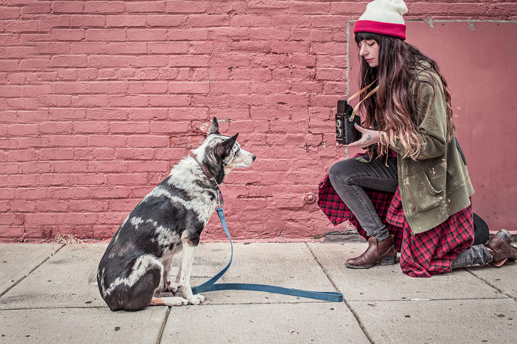 Woman taking photo of a dog 1050x700px