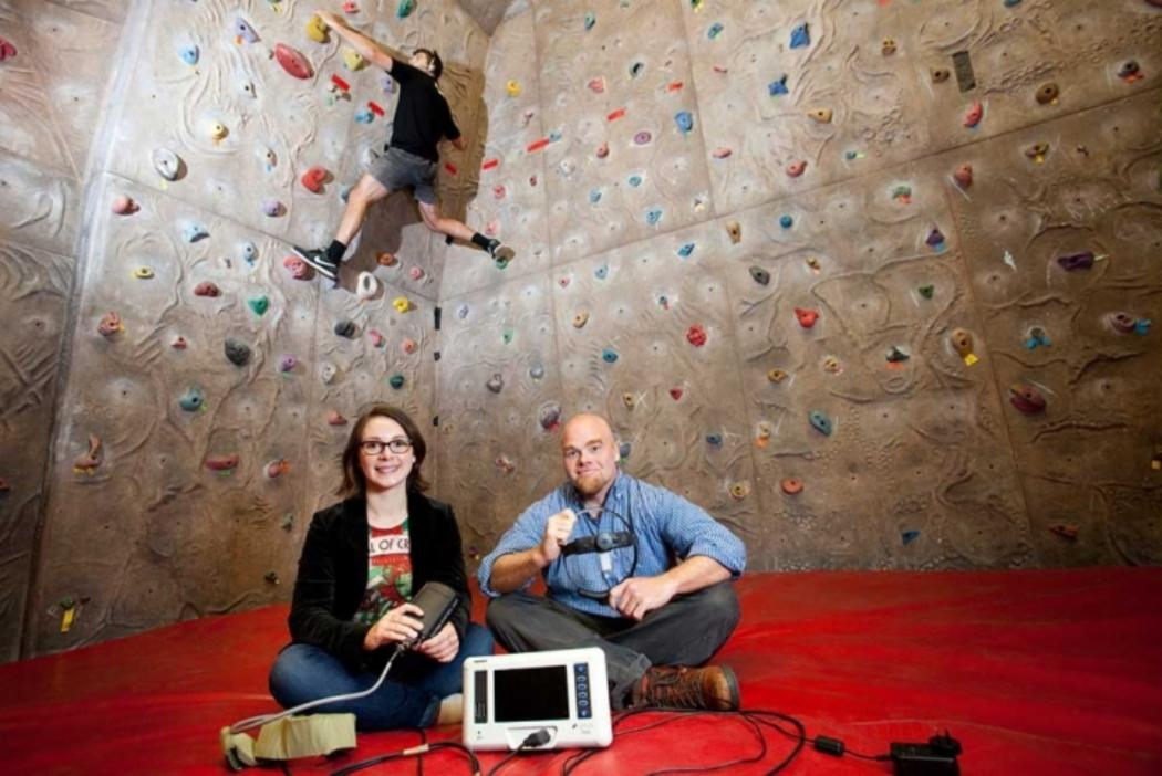 masters students researching at a rock climbing wall